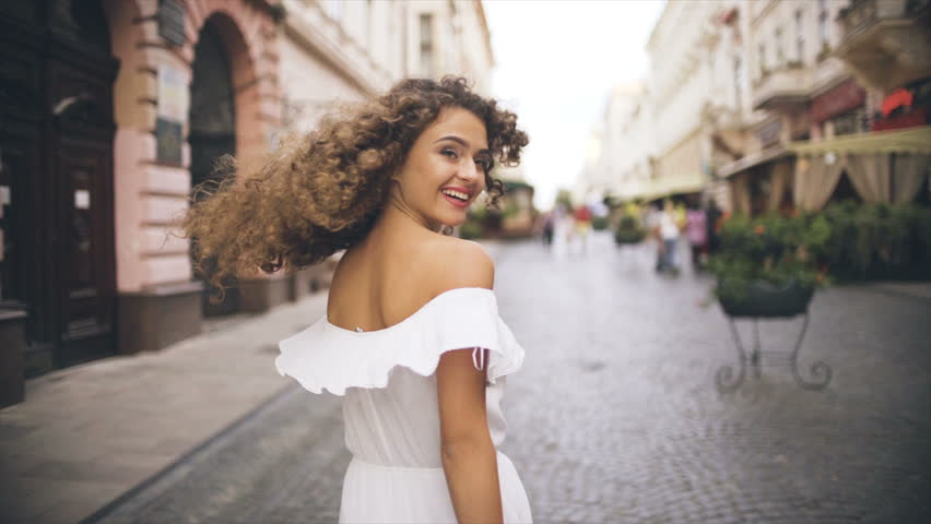 The curly woman walking outdoor. slow motion | Shutterstock HD Video #1013898623