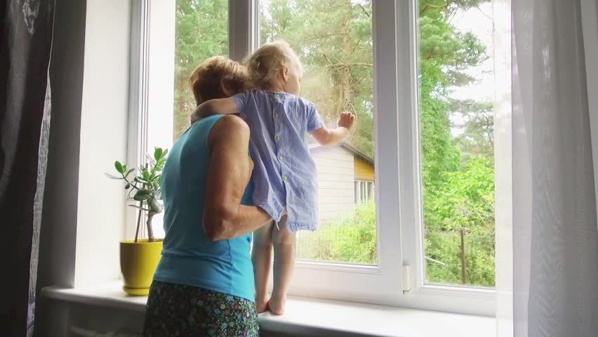 Grandmother playing and taking care of child at home. looking through the window | Shutterstock HD Video #1013899175