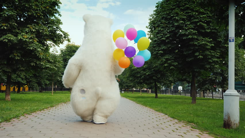 Rear view: A large polar bear walks down the street, carries balloons and a box with a gift. Birthday gifts and a cool party concept