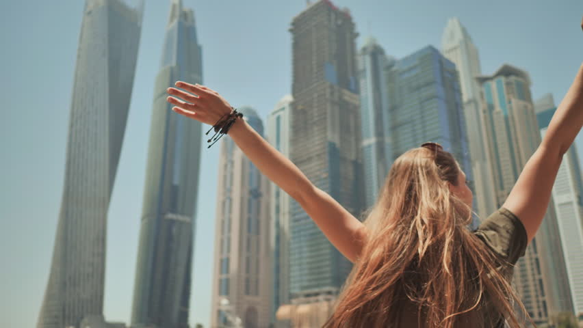 A happy girl is in Dubai on a background of skyscrapers Dubai Marina. | Shutterstock HD Video #1013900252