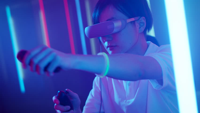 East Asian Pro Gamer Wearing Virtual Reality Headset Plays Online Video Game with Joysticks / Controllers. Cool Retro Neon Colors in the Room. Shot on RED EPIC-W 8K Helium Cinema Camera. #1013902904