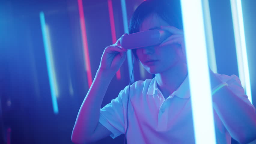 East Asian Pro Gamer Puts On Virtual Reality Headset Plays Online Video Game with Joysticks / Controllers. Cool Retro Neon Colors in the Room. Shot on RED EPIC-W 8K Helium Cinema Camera. #1013902919
