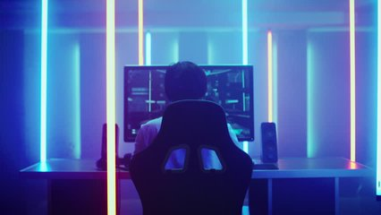 Back View Shot of the Professional Gamer Playing in First-Person Shooter Online Video Game on His Personal Computer. Room Lit by Neon Lights in Retro Arcade Style.  Shot on RED EPIC-W 8K Helium Camera