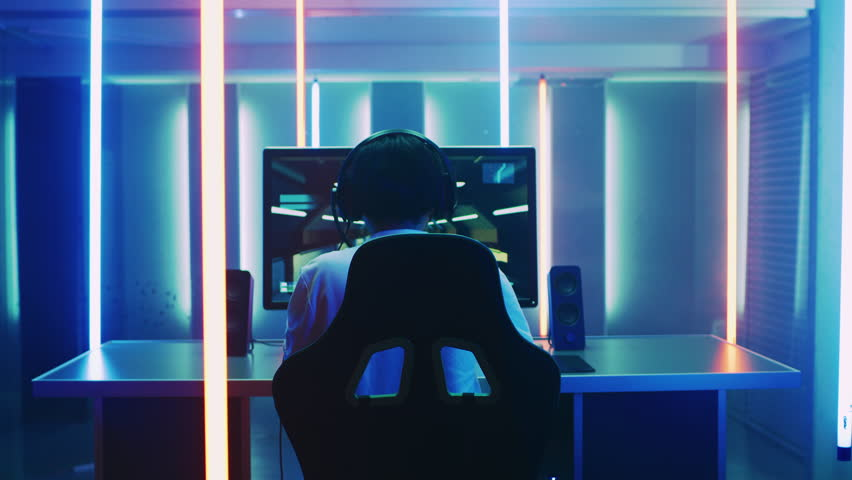 Back View Shot of the Professional Gamer Playing in First-Person Shooter Online Video Game on His Personal Computer. Room Lit by Neon Lights in Retro Arcade Style. Online Cyber e-Sport Championship. | Shutterstock HD Video #1013903813