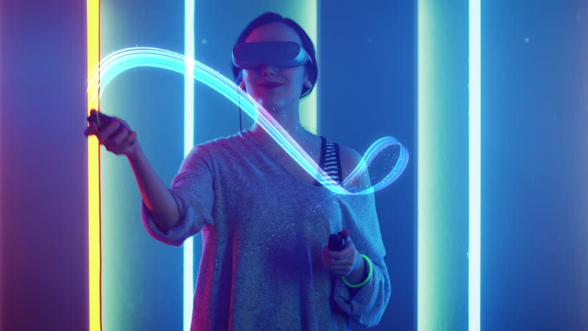 Beautiful Young Girl Wearing Virtual Reality Headset Draws Abstract Lines and Figures with Joysticks / Controllers. Creative Young Girl Does Concept Art with Augmented Reality. Shot on 4K UHD. | Shutterstock HD Video #1013903834