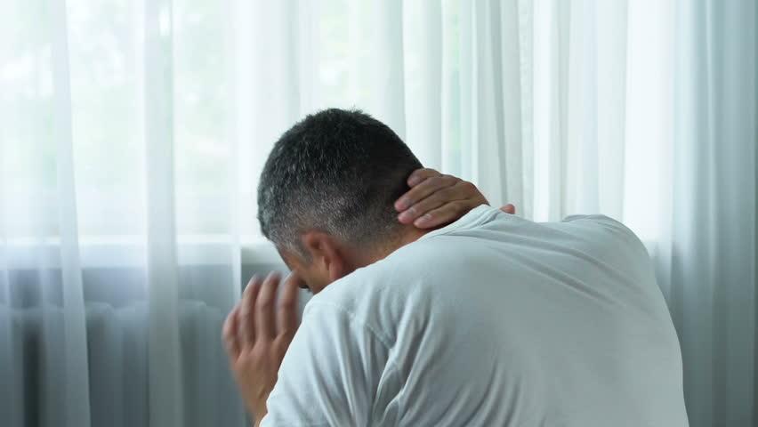 Adult man suffering sharp neck pain, massaging muscle spasm, health problem
