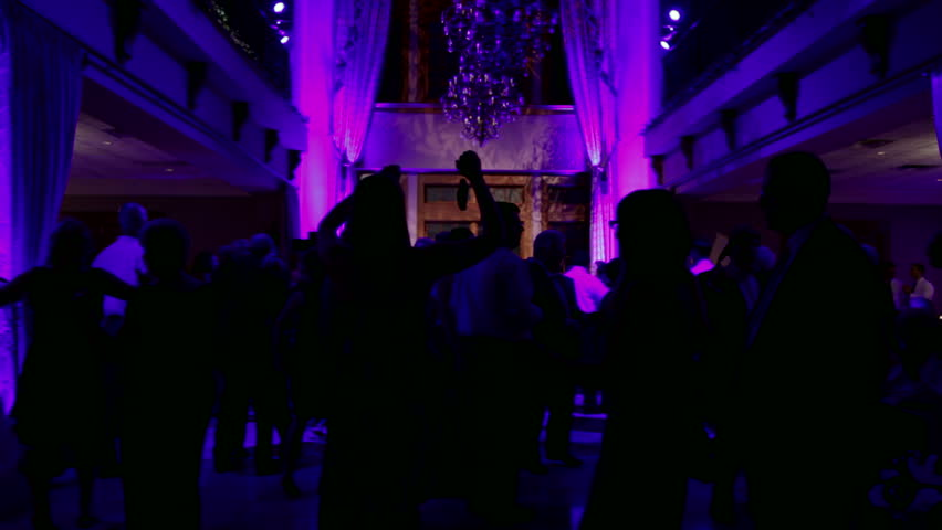 Group of silhouetted people dancing in a dark banquet hall for a wedding reception.