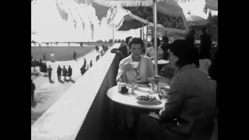 CIRCA 1960s - Two American teachers get lunch at the 1964 New York World's Fair before photographing different international pavilions.