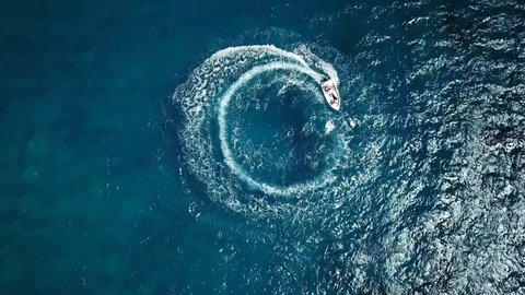 Speed motor boat creating cyrcle at sea. Aerial view from drone.