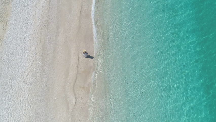 Aerial - Top view of woman in a dress walking on paradise beach Royalty-Free Stock Footage #1013926073
