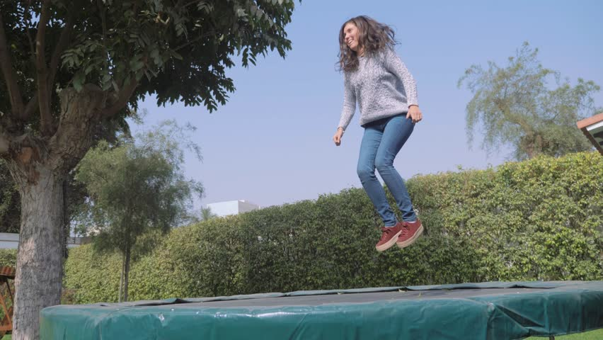 Beautiful hispanic young woman jumping and celebrating on trampoline in the backyard, slow motion. Concept of freedom or sucess.