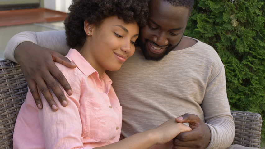 Happy african couple hugging on bench, outdoor date in city cafe, closeness #1013928731