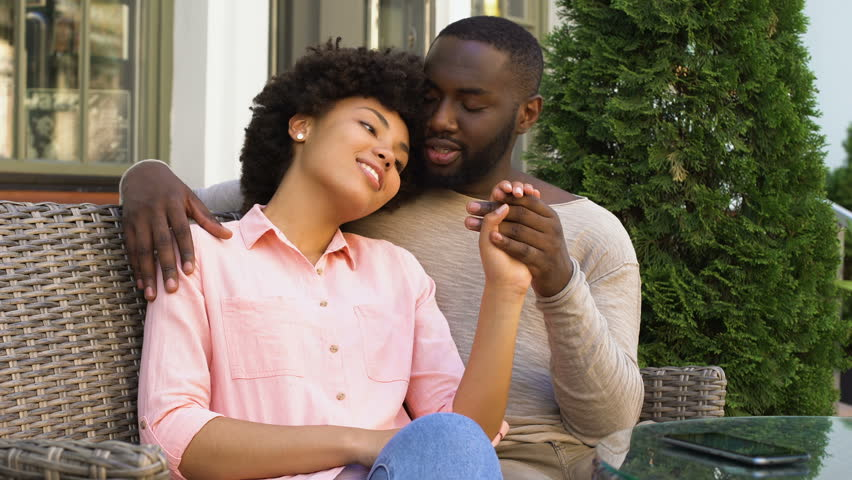 Cute afro-american couple relaxing in outdoor cafe, hugging and talking, love #1013928734