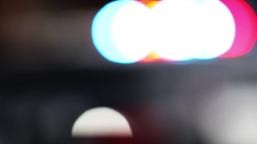 Close up of flashing police lights blurred and out of focus. Emergency light of a cop car flashing in a bokeh pattern. Crime scene investigation.    Shutterstock HD Video #1013933216