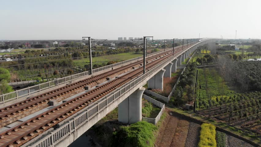 Jiashan, China-2018: Aerial of raised railway of Chinese high speed rail. China's bullet train CSR zooming through the rural countryside. Drone shot of moving Gao Tie on elevated railway.