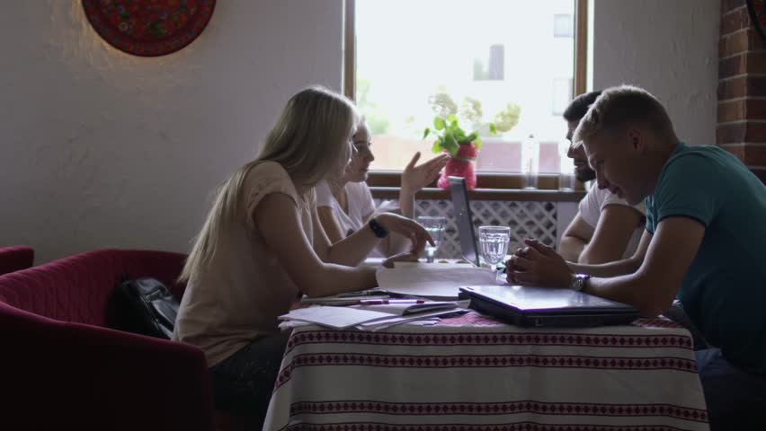 Group of people sit in restaurant and converse | Shutterstock HD Video #1013952593