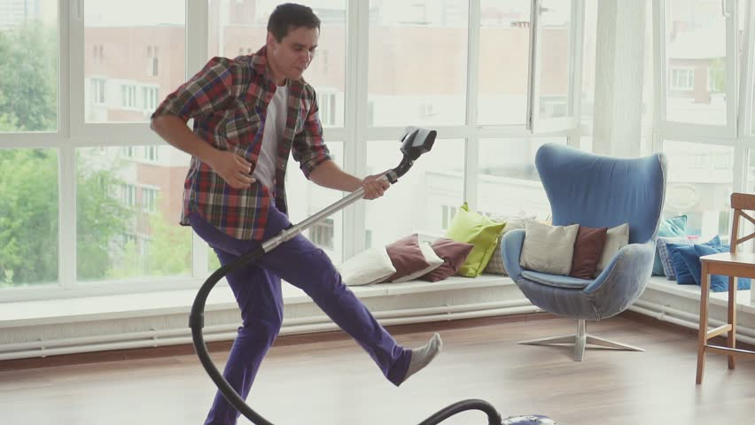 Man doing the cleaning vacuums and have fun dancing.Slow mo #1013960117