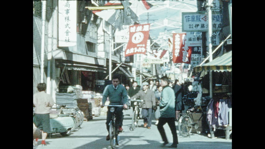 1950s JAPAN: People walk and ride bicycles through vendor street in Osaka. Man demonstrates abacus to customers. Bunraku theater.
