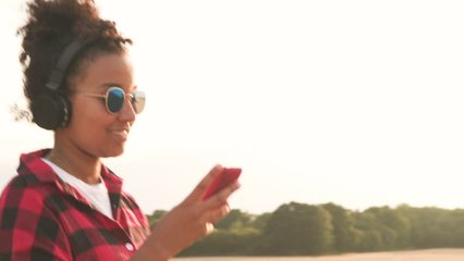 Tracking video clip of beautiful mixed race African American girl teenager young woman wearing a red and black shirt and blue sunglasses walking listening to music on wireless headphones at sunset
