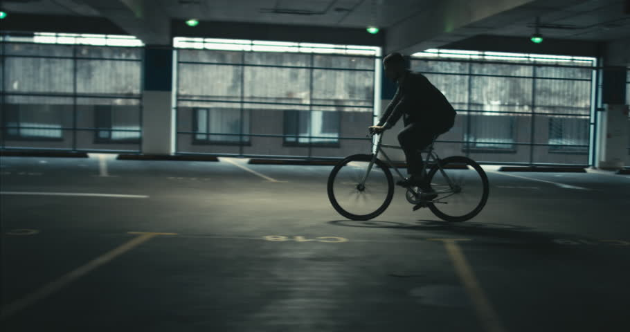 TRACKING Handsome young adult man wearing suit riding his classic bicycle to work through an empty parking garage. 4K UHD