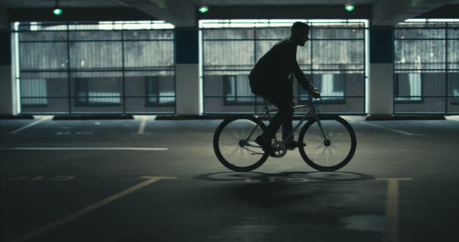TRACKING Handsome young adult man wearing suit checking phone before riding his classic bicycle to work through an empty parking garage. 4K UHD 60