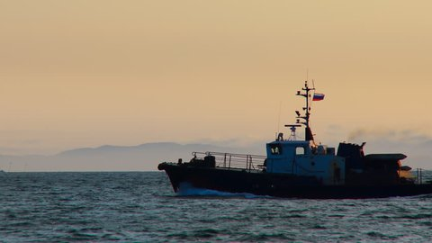 A small ship swiftly swims along the sea waves in the rays of the evening sun