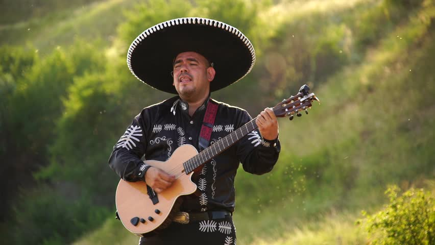 Mexican musician mariachi in traditional costume with sombrero plays guitar.