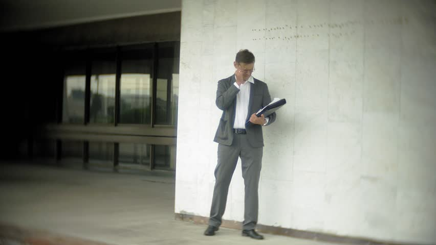 Businessman in the city. He wears a suit and briefcase. He looks through documents and talks on the smartphone 4k | Shutterstock HD Video #1014002864