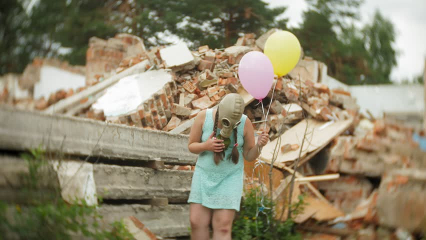 A little girl in a gas mask walks through the ruined buildings with balloons in her hand 4k | Shutterstock HD Video #1014003086