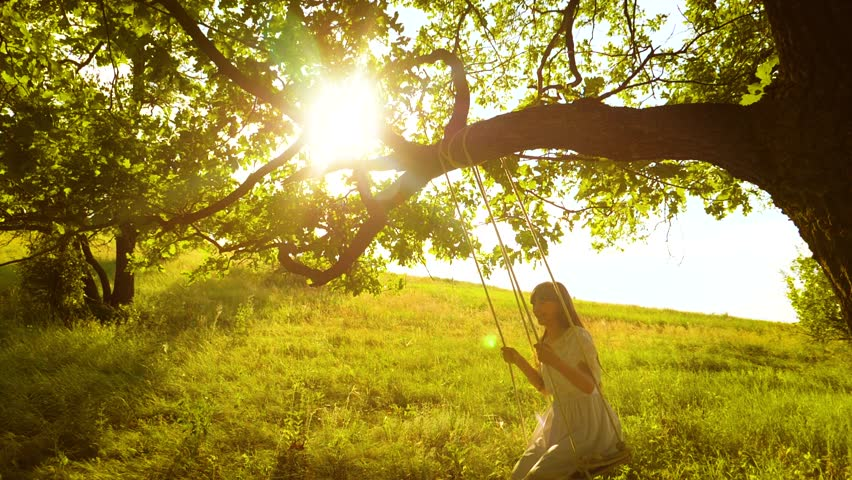 Happy girl with long hair, swinging on swing in bright rays of golden sunset and smiling. Slow motion. #1014004289