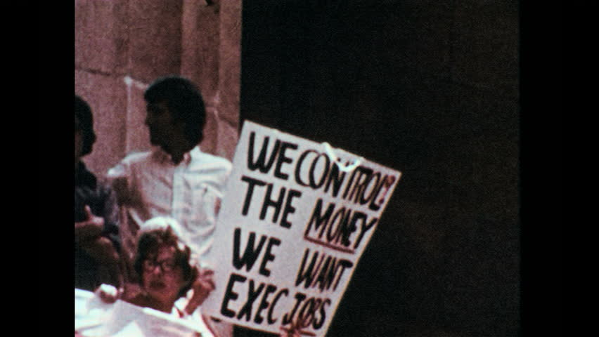 1960s: Women stand on steps, hold banner, chant. Woman holds sign, smiles. Man in navy uniform confronts man.