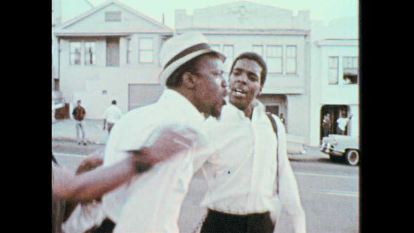 1960s: Man yells angrily, lunges forward, another man holds him back. Police clash with crowd. People march and protest in the street.