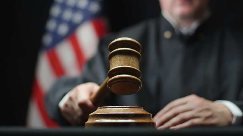 Judge's hand with wooden gavel hammering against American flag in United States court