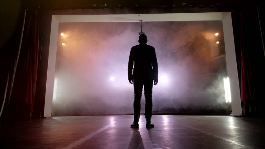 Showman. Young male entertainer, presenter or actor on stage. Back, arms to sides, smoke on background of spotlight. Rear view of a male public speaker speaking at the microphone, pointing, in the #1014025064