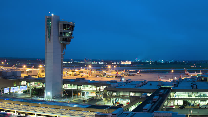 PHILADELPHIA, PA - 2018: PHL International Airport Night Timelapse with ATC Air Traffic Control Tower Overlooking Terminal Exterior with Streaking Lights from Airliners Moving at Concourse Gates