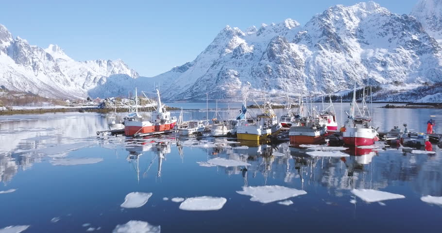 Aerial panorama drone view of beautiful Lofoten Islands winter scenery with traditional fishing boats lying in harbor on a cold sunny day with scenic blue sky, Norway, Scandinavia, northern Europe