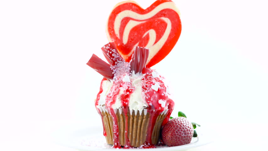 Red and white theme colorful novelty cupcake decorated with candy and large heart shaped lollipop for Valentine's, Mother's Day and birthday celebration. | Shutterstock HD Video #1014037136