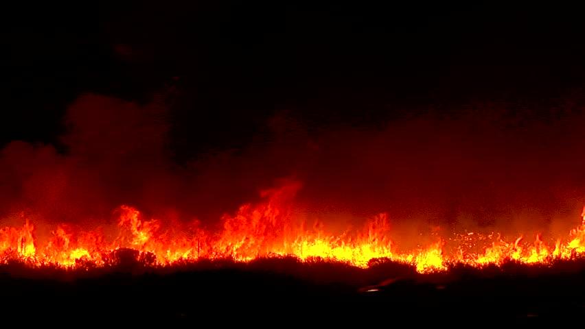 2017 - the Thomas Fire burns at night in the grass above the 101 freeway near Ventura and Santa Barbara, California.