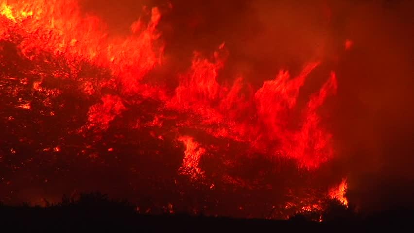 2017 - the Thomas Fire inferno burns at night in the grass above the 101 freeway near Ventura and Santa Barbara, California.