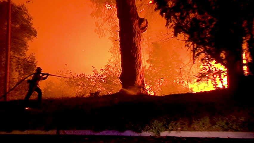 2018 - A firefighter stands in silhouette and fights a huge hillside blaze during the Holiday Fire in Goleta, California.