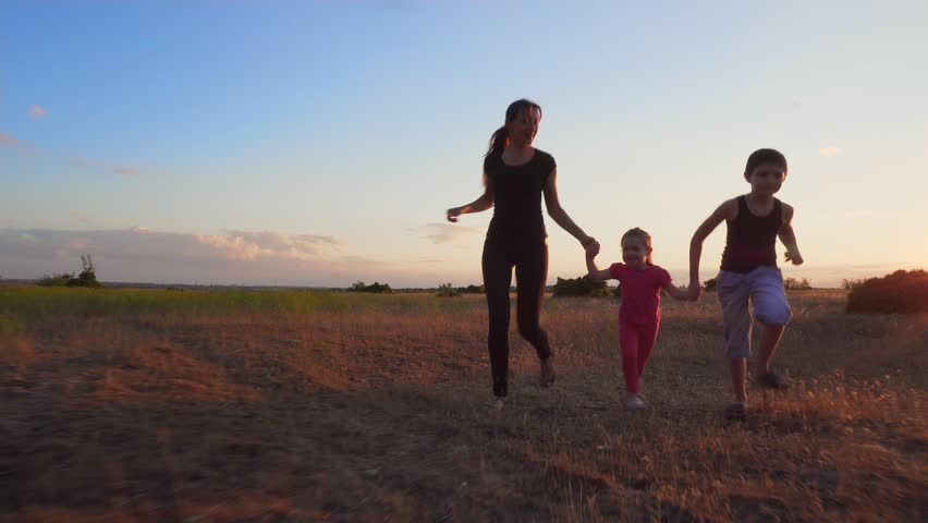 Young family holding hands and running at sunset #1014060335