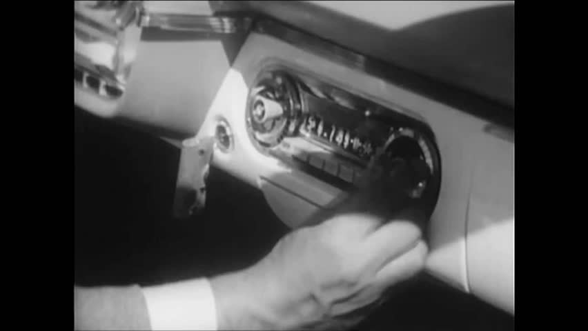 CIRCA 1950s - A driver tunes his car radio to an emergency broadcast during an evacuation of Portland, Oregon in anticipation of an atomic attack.