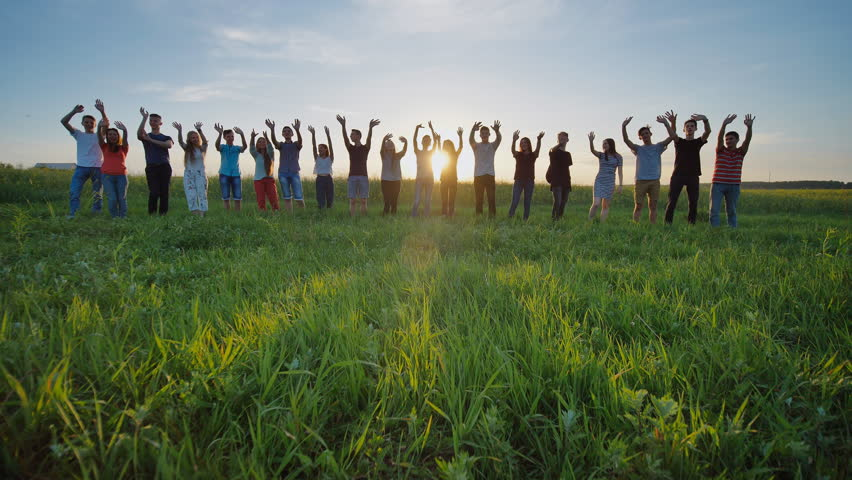 Students say goodbye to the school. Pupils waving their hands against the backdrop of the setting sun.