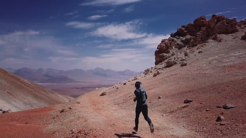 Male athlete running on the high mountain trail of the rocky desert in the Atacama desert. Aerial view, 4k