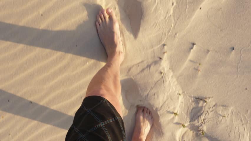 Barefoot male legs walking on sand dune in Sahara desert