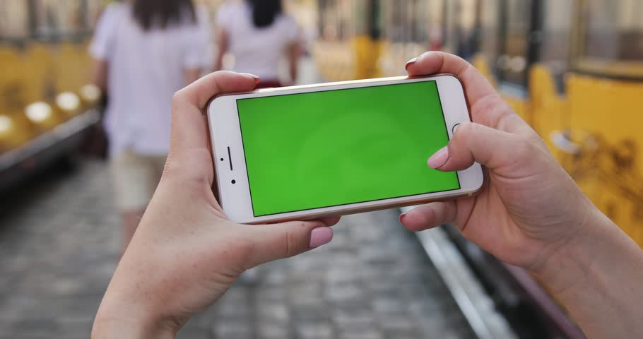 PARIS, FRANCE- APRIL 05, 2017: Close up woman hand holding use mobile smart phone with horizontally green screen touch display  | Shutterstock HD Video #1014104435