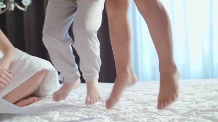 Excited Kids Jumps On Bed. Parents are happy with the children. Happy Children In The Morning.