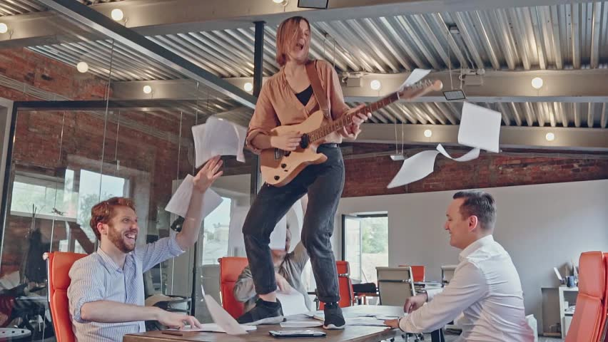 Happy successful start-up business team have fun dancing party in modern office throwing paper documents and celebrating success of project