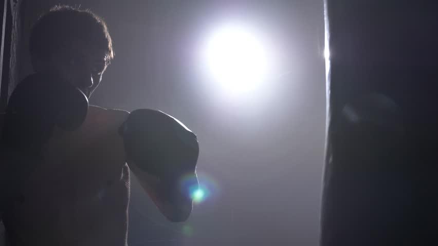 Shirtless kickboxer shadow boxing punching bag, training for big fight, smoke everywhere #1014113147
