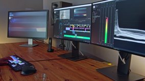 Video editor sitting in a dark editing suite working on a video project